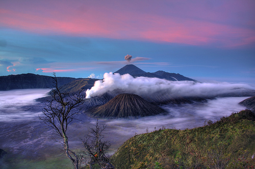 Mt. Batok dormant inMt. Bromo belching sulphur to the left, the dormant Mt. Batok in the foreground, and Mt. Semeru erupting in the distance. Photo: flickr member isa_adsr